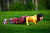 Press ups exercise by young woman. Girl working out on grass crossfit strength training in the glow of morning sun — Stock Photo