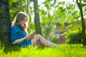 Pretty young caucasian woman  sitting outside under a tree talking on smartphone device. Filtered effects — Stock Photo