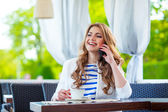 Young woman at cafe drinks coffee and talking on the mobile phone — Stock Photo