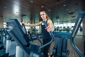 Portrait of pretty girl training on special sport equipment in gym — Stock Photo