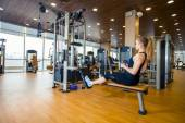 Sport, fitness, lifestyle and people concept - young woman flexing muscles on gym machine — Stock Photo
