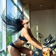 Beautiful woman at the gym on bike, cycle, hair — Stock Photo #74782895