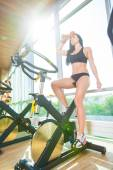 Beautiful woman at the gym on bike, cycle, sunny gym, general plan, weary — Stock fotografie