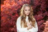 Güzel kıvırcık saçlı genç kadın bir arka plan kırmızı ve sarı sonbahar yaprakları — Stok fotoğraf