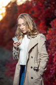 Young beauty woman writing message on cell phone in a autumn park — Stock Photo