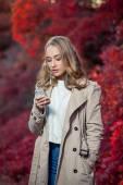 Jeune beauté femme écriture message sur téléphone portable dans un parc en automne — Photo
