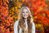 Beautiful young woman with curly hair against a background of red and yellow autumn leaves, happiness, laughter , smile — Stock Photo