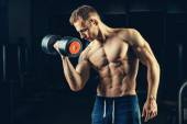 Athlete muscular bodybuilder training back with dumbbell  in the gym — Stock fotografie