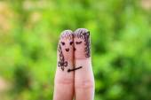 Face painted on the fingers.  woman is kissing his girlfriend on the cheek — Stock Photo