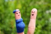 Gesicht gemalt an fingern. glückliches paar ist die frau schwanger. — Stockfoto