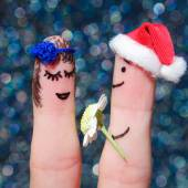 Face painted on the fingers. Man is giving flowers to a woman — Stockfoto