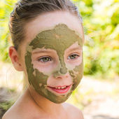 Close up of beautiful girl with facial clay mask — Stock Photo
