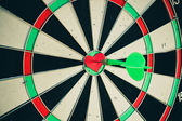 Darts arrow in the target center of the heart. Toned image. — Stock Photo
