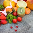 Fruits, vegetables and in measure tape in diet on wooden background — Stock Photo #57174149
