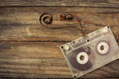 Audio cassette on the old wooden background. Toned image. — Stock Photo