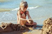 Girl playing with sand on the sea shore. Toned image — Stock Photo