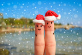 Finger art of a Happy couple. Happy couple in Christmas hats resting on the sea — Stok fotoğraf