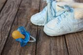 Baby shoes and a pacifier on the old wooden background. — Stock Photo