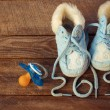 2015 year written laces of children's shoes and a pacifier on the old wooden background. Toned image — Stock Photo #60103095