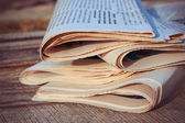 Newspapers on old wood background. Toned image. — Stockfoto