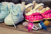 Baby shoes and pacifiers pink and blue on the old wooden background. Toned image. — Stock Photo