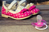 Baby shoes and a pacifier on the old wooden background. Toned image — Stock Photo