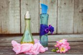Blue and green perfume bottles near flowers fresia. Toned image. — Stock Photo
