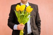 A man wearing business suit, holding bouquet of yellow tulips. — Stock Photo