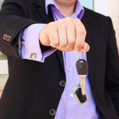 A man in a business suit holding key with remote control — Stock Photo