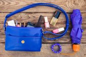 Blue women's purse. Things from open lady hand bag. Toned image. — Stock Photo