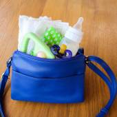 Women's handbag with items to care for the child: bottle of milk, disposable diapers, rattle, pacifier and baby clothes. — Stock Photo