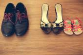 Three pairs of shoes: men, women and children. Baby sandals stand next to women's shoes. concept of the child is friends with his mother. Idea parents divorced, child remained with mother. Toned image — Stock Photo
