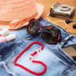 Summer women's accessories: red sunglasses, beads, denim shorts, mobile phone, headphones, a sun hat, camera, nail polish, perfum. Toned image — Stock Photo #76229063