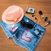 Summer women's accessories: red sunglasses, beads, denim shorts, mobile phone, headphones, a sun hat, camera, nail polish, open lipstick, perfum,. Toned image — Stock Photo