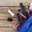Things from open lady handbag. womens purse on wood background. Cosmetics and womens accessories fell out of the blue handbag. — Stock Photo #78094850