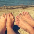 Female and male feet on the background of blue sea. couple lying and resting on the beach. The concept of a man meets a woman - a holiday romance. — Stock Photo #78978072