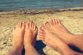 Female and male feet on the background of blue sea. couple lying and resting on the beach. The concept of a man meets a woman - a holiday romance. — Stock Photo