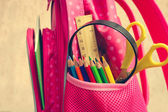 Stationery objects. School supplies are in school backpack. Toned image. — Stock Photo