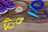 Sports equipment: the birdie is on the racket, skipping rope, swimming goggles and sneakers on wooden background — Stock Photo