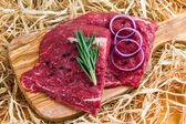 British Beef Flat Iron steak on cutting board and straw, rosemary and onion — Stock Photo