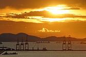Silhouette of port warehouse and crane bridge — Stock Photo