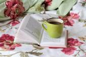 Mug with book on the bed linens flowered — Stock Photo