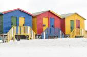 Colorful beach huts in a row on the beach in winter painted red green blue and yellow — Stock Photo