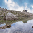 Italian Alps in Val Badia, Reflection of a mountain shelter in a lake — Stock Photo #54608575