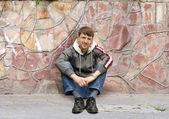 Man sits on the sidewalk — Stock Photo