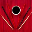 Chopsticks and bowl with soy sauce on bamboo mat — Stock Photo #55028813