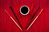 Chopsticks and bowl with soy sauce on bamboo mat — Stockfoto