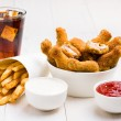Chicken wings, french fries, coke and sauces on the table — Stock Photo #56338025