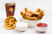 Chicken wings, french fries, coke and sauces on the table — Stockfoto