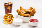 Chicken wings, french fries, coke and sauces on the table — Stock Photo